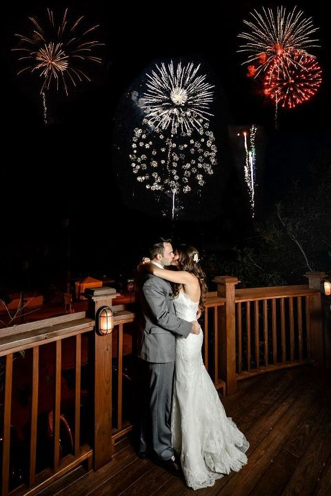 Firework explode while a newly married couple kisses on the deck of 128 South events.