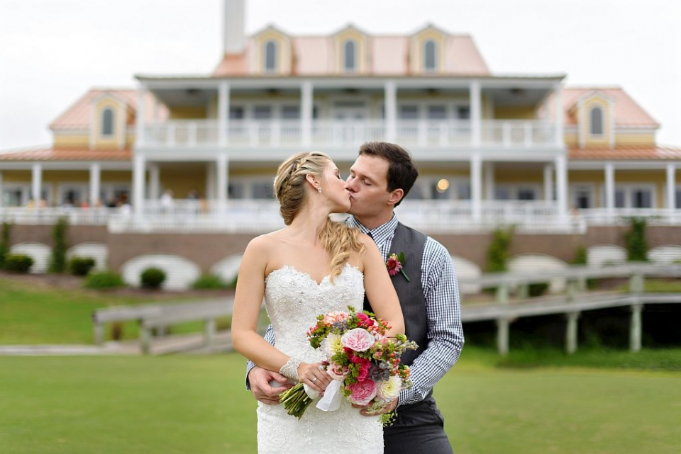 A bride & groom kiss in front of Bricklanding.